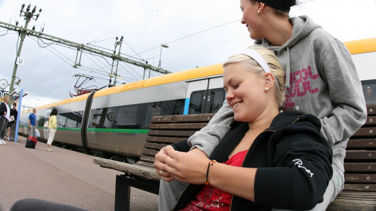 Unga kvinnor sitter på bänk på tågstation
